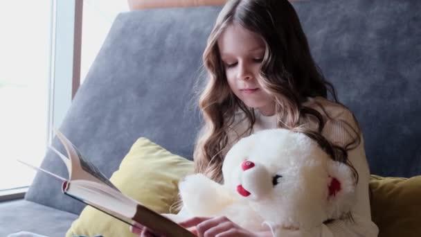 Egy aranyos kislány ül a kanapén egy plüssmackóval és könyvet olvas.