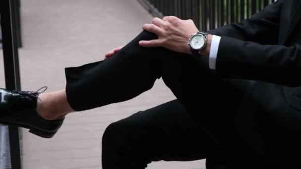 Obchodní muž sedí v luxusním obleku a boty se zkříženýma nohama.