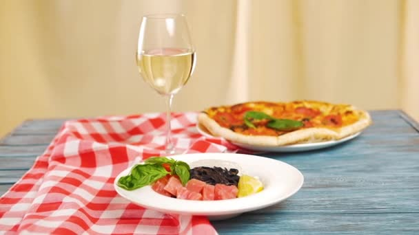 Tintenfischnudeln mit Lachsfisch, Zitrone und Basilikum in einem weißen Teller auf einem Holztisch. Serviert mit einem Glas Weißwein. Kamera bewegt sich langsam über Schüssel. Nahaufnahme, hohe Qualität.