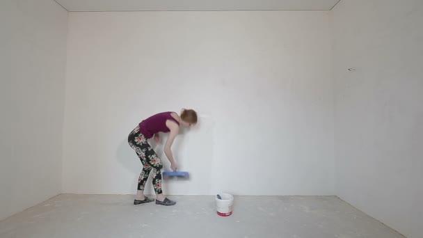mladá dívka Omítání zdí s lopatkou v jejím domě