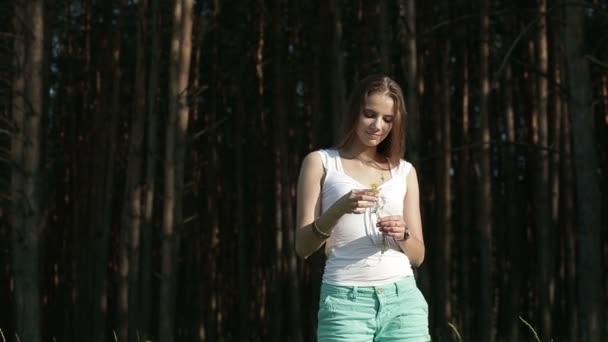 Porträt eines schönen Mädchens im Kiefernwald inmitten von Blumen