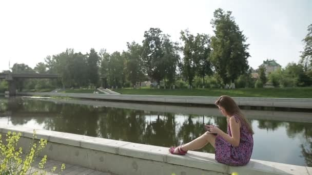 Young girl write something in her notebook on river bank in city park