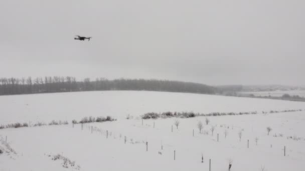 Před kamerou se vznáší černý dron..