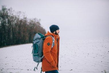 bearded man walking on winter field