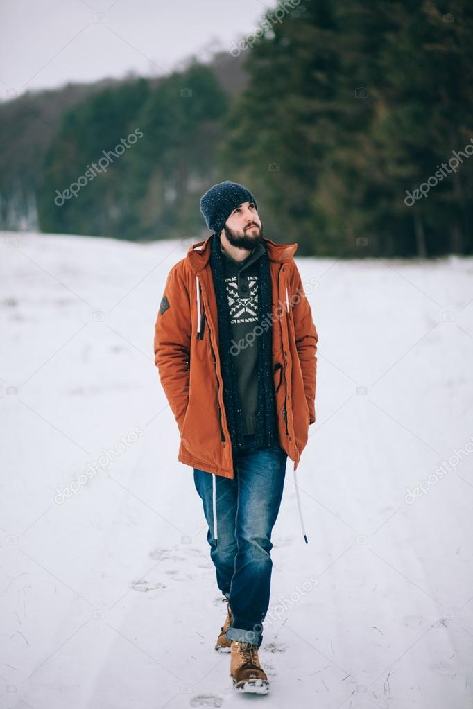bearded man walking on the road in winter