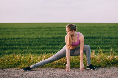 Blond woman stretches the body