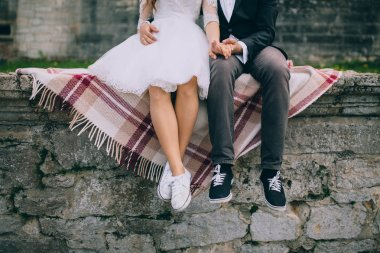 Newlyweds sitting by the stairs of old castle