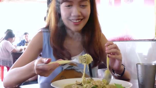 Mladá žena jíst nudle