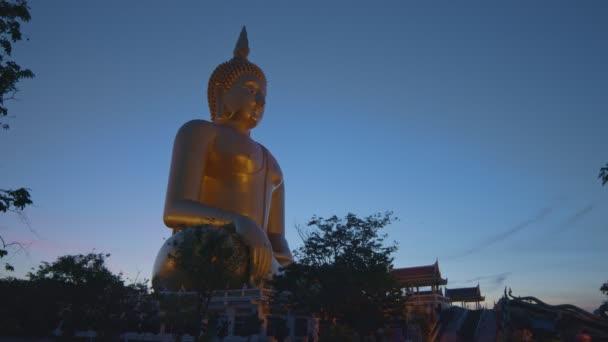 Thaiföld nagy Buddhája előtt a Wat Muang Ang Thong Thaiföldön. A világ legnagyobb Buddha szobra messziről látható, rizsföldekkel körülvéve.