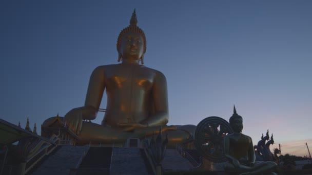 před velkým Buddhou Thajska na Wat Muang Ang Thong Thajsku. Největší socha Buddhy na světě je vidět z dálky, obklopená rýžovými poli.