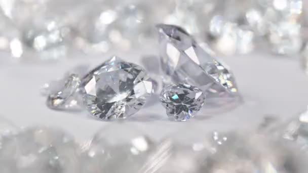Bílé diamanty různých velikostí jsou umístěny ve středu kruhu a točí se na bílém pozadí obklopeném bílými diamanty.