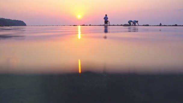 Die Reflexion der Sonne auf der Wasseroberfläche bei Sonnenuntergang am Nai Yang Beach Phuket