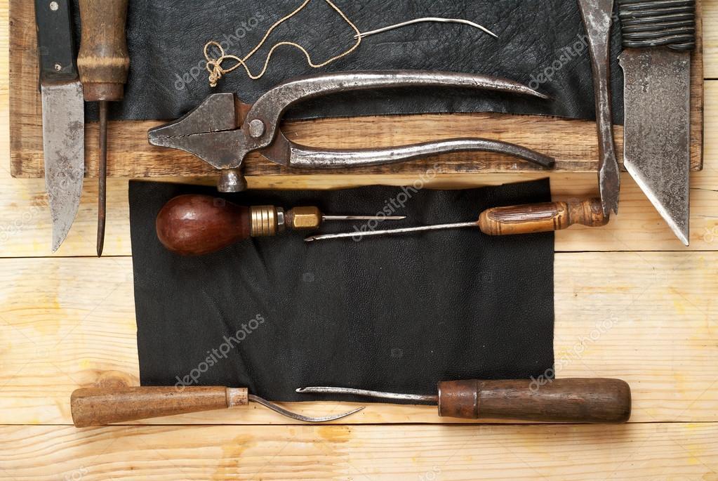 Kožené řemeslné nástroje na dřevěné pozadí. Craftmans pracovní stůl. Kus  kůže a ručně vyráběných nástrojů. Pohled shora– stock obrázky 2fd43e2165