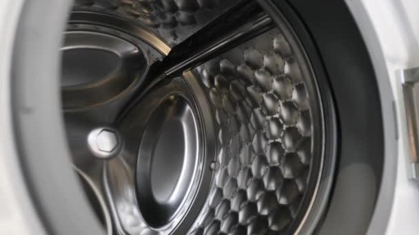Kamera se pomalu pohybuje podél otevřené pračky a ukazuje svůj interiér