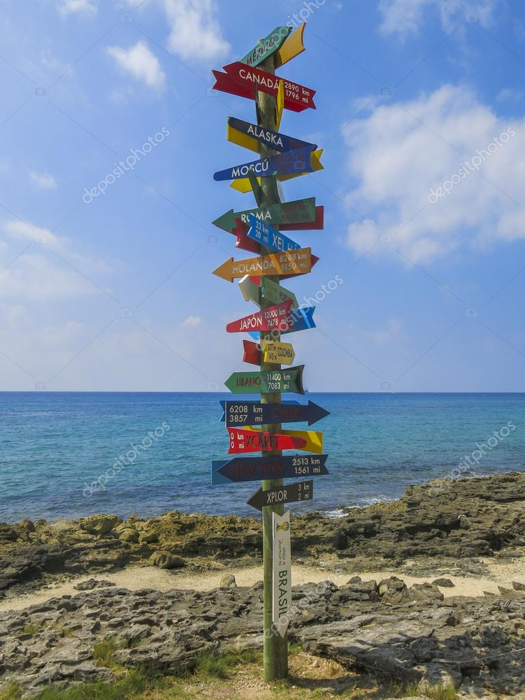 Signpost pointing at different cities