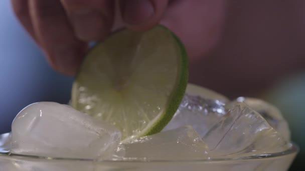 Nahaufnahme des Hinzufügens einer Limette zu einem Eiscocktail