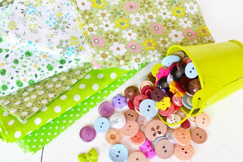 Stoffstücke in Blumen- und Polka Dot Muster. Kleine grüne Eimer mit ...