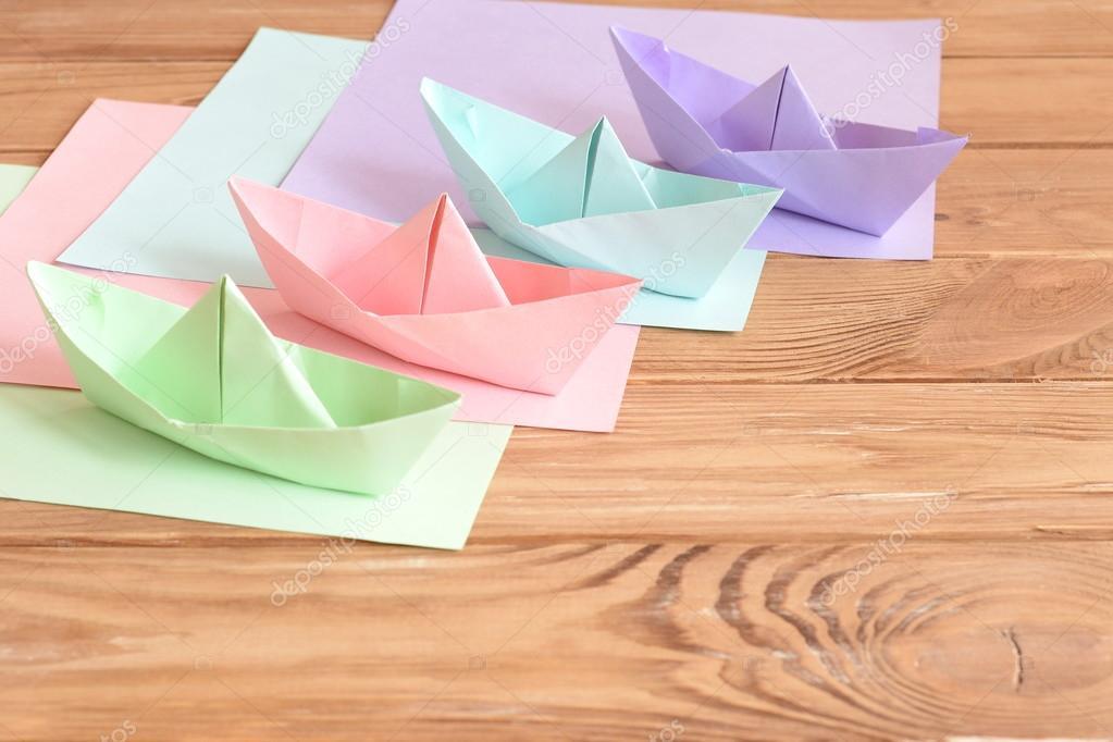 Cuatro color origami juguetes de barcos sobre una mesa de madera ...