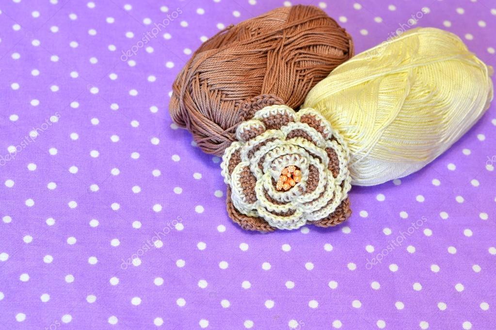 Gehäkelte Blume, zwei Knäuel Baumwollgarn. Hintergrund mit ...