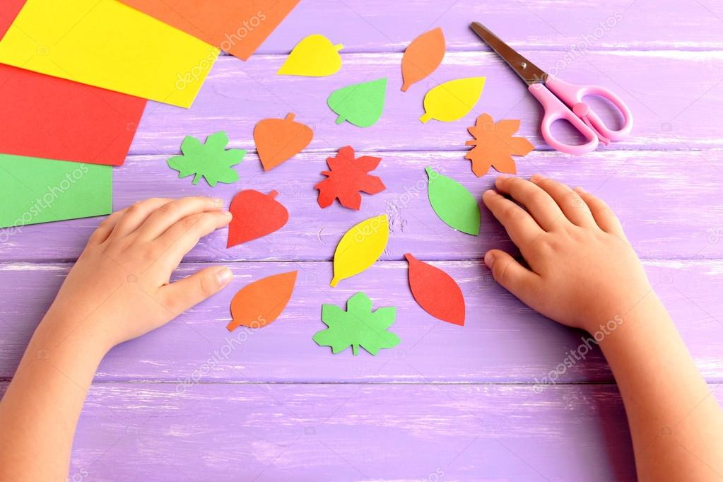 Niño corte de hojas de otoño de papel de color. Niños haciendo ...