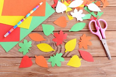 Autumn colorful leaves cut from paper, pencil, scissors, colored paper sheets on a wooden background. Teaching scissor cutting. Early learning in kindergarten and at home. Kids art