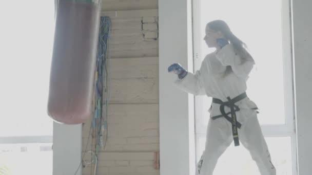 Slow motion Taekwondo dívka vlaky s boxovací pytel v The Gym