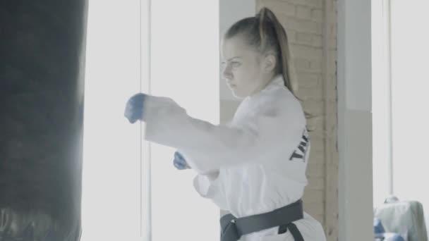 Slowmotion Taekwondo lány vonatok boxzsák a tornateremben