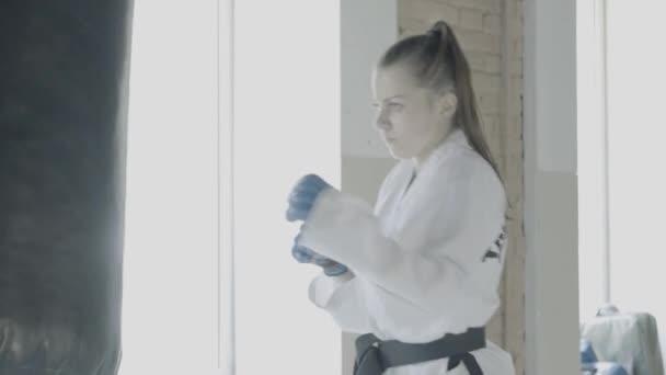 Taekwondo dívka vlaky s boxovací pytel v tělocvičně