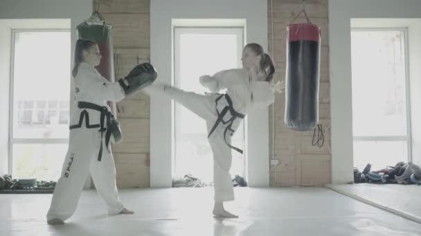 Two Taekwondo Girls Train For A Kick On Boxing Paw