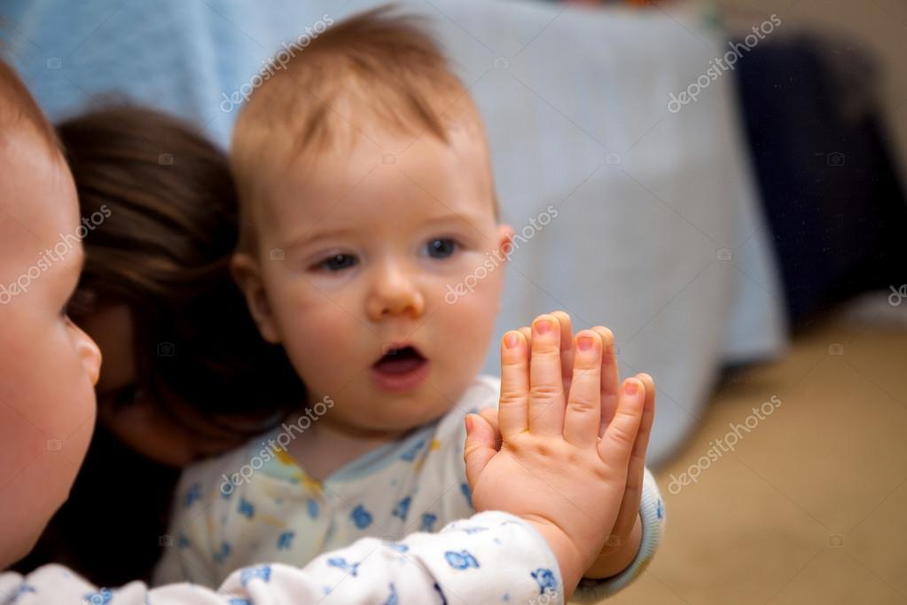 Beb tiene su mano en un espejo y es sorprendido por la reflexi n fotos de stock jbrown777 - Espejo para bebes ...
