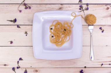 A plate of spaghetti with thread on a wooden background, ball of thread on a fork