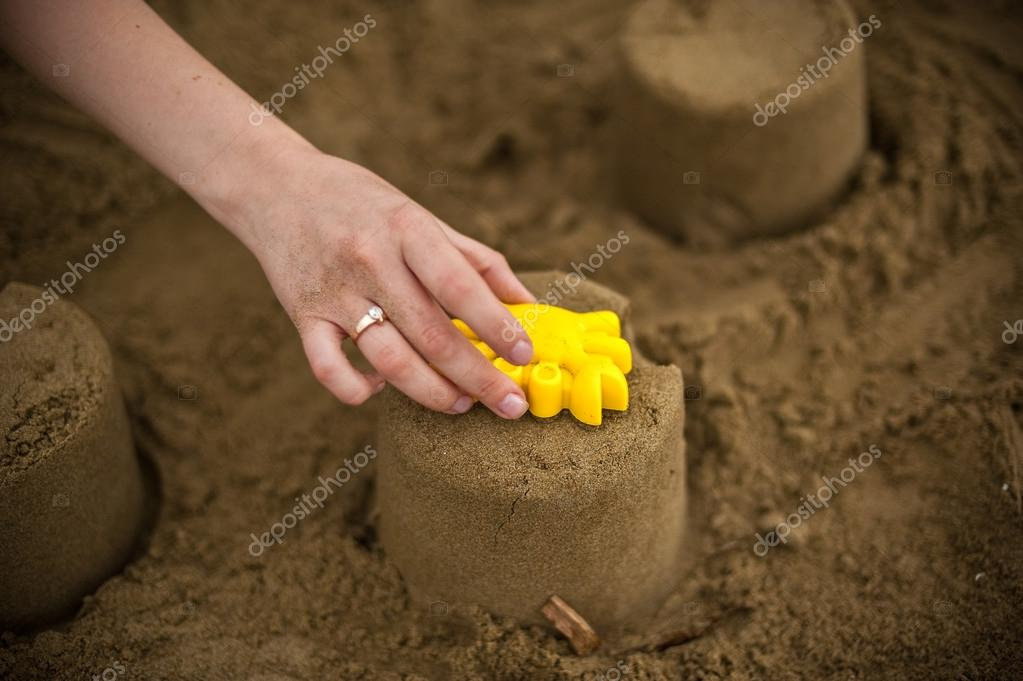 Hand making a sand mold using molds