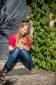 Fotografie Rusovlasá dívka s kočkou sedí na verandě