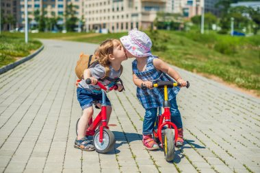 Toddlers Boy and girl kissing on balance bikes in summer park