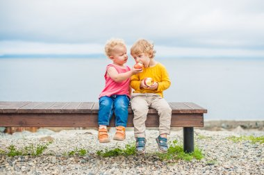 Toddlers boy and girl sitting on a bench eat an apple