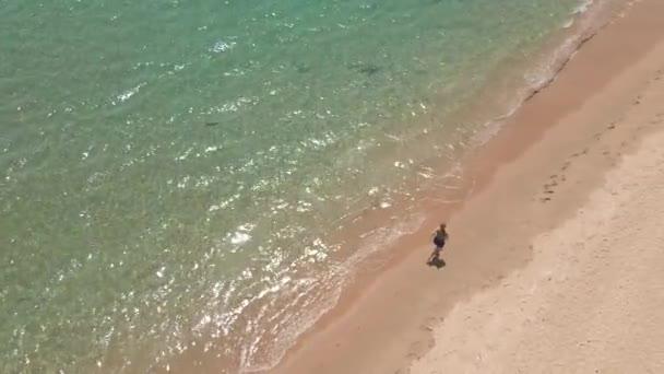 Zpomalení letecké záběry mladé ženy běží na krásné pláži. Koncept zdravého životního stylu a sportu
