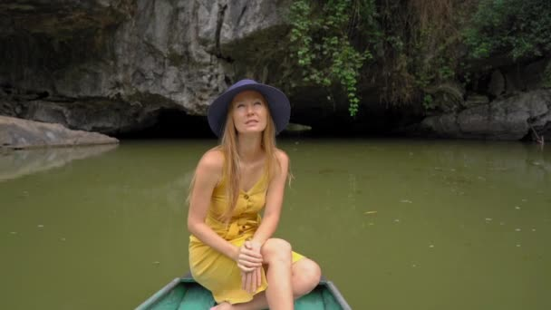 Slowmotion shot of a young woman on a boat having a river trip among spectacular limestone rocks in Ninh Binh, a tourist destination in northern Vietnam. Travel to Vietnam concept