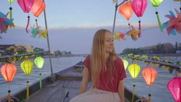 A young woman tourist visits an ancient town of Hoi An in the central part of Vietnam. She is taking a ride on a boat decorated with glowing colourful lanterns. Travel to Vietnam concept