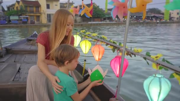 A young woman and her son tourists visit an ancient town of Hoi An in the central part of Vietnam. They are taking a ride on a boat decorated with glowing colourful lanterns. Travel to Vietnam concept