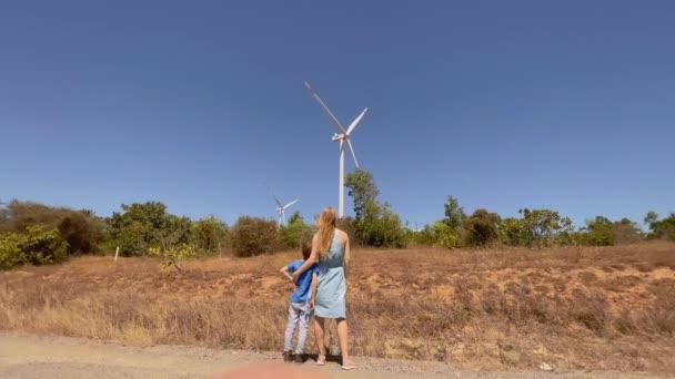 Zpomalený výstřel. Mladá žena a její syn navštíví farmu větrných turbín v semidesertním prostředí. Koncept větrné energie