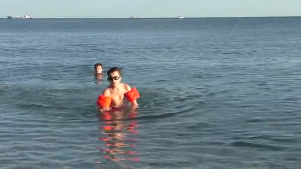 Little Boy in Glasses and Orange Inflatable Sleeves is Going Out From Sea and Throwing Stone to Camera Side