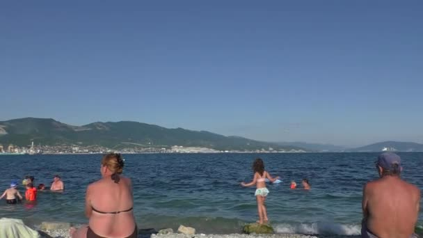 Sunbathing People Are Sitting Back to Camera, Looking at Sea and Coastline of City and Mountains in Sunny Day