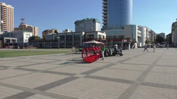Malé červené a černé vozidla pro zábavu jsou připraveny v centru města v slunečný letní den