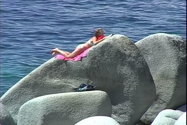 Dívka sunbathes na skále při čtení knihy