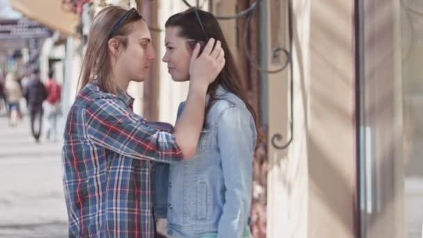 Roztomilý dívka a chlapec s dlouhými vlasy, líbání na ulici