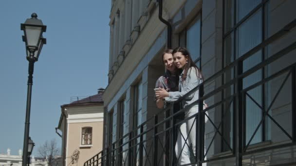 Cute girl and boy with long hair stands near building, study the route on a map on the gadget