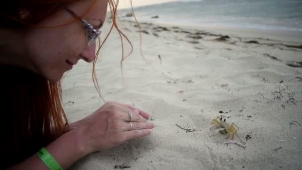 Mladá atraktivní žena s červenými vlasy v brýlích hraje s krab na pláži, close-up, dominikánský Republick