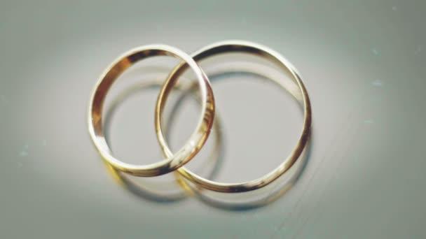 Svatební prsteny lež na šedém pozadí, odlesky od světla