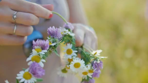 Young woman collects a wreath of daisies in meadow of flowers, close up