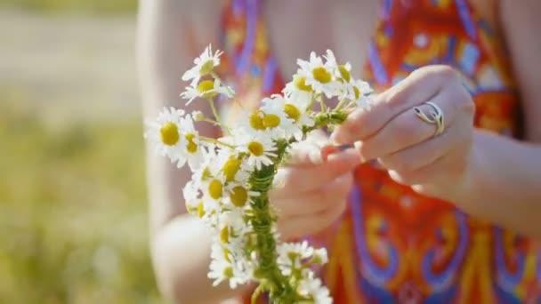 Žena v červených šatech shromažďuje věnec z květin v lučních květin, velmi zblízka